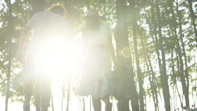 A young woman and a mid adult man walking among trees