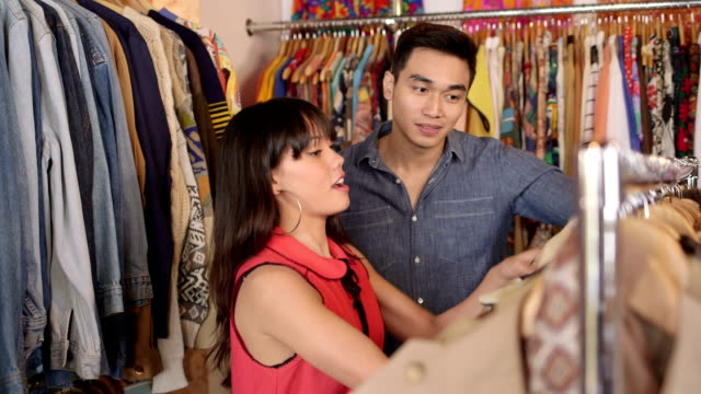 mcu a young woman and a young man browse through a shop of colourful vintage clothing - 輪っかのイヤリング点の映像素材/bロール