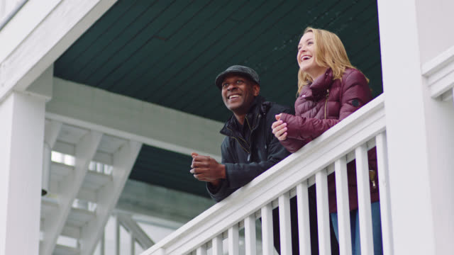 ms slo mo. young woman and african american man in winter coats laugh and talk as they lean over outdoor porch balcony. - heterosexual couple stock videos & royalty-free footage