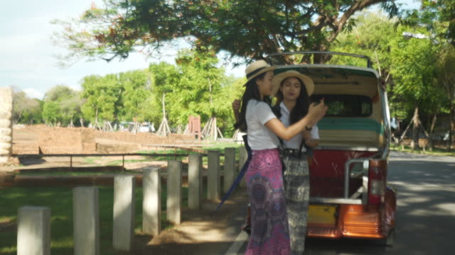 タイのアユタヤで寺院を探索する若い女性と友人。若い観光客の女性が歩き回り、古代の歴史建築の景色を楽しんでいます。 - アユタヤ県点の映像素材/bロール