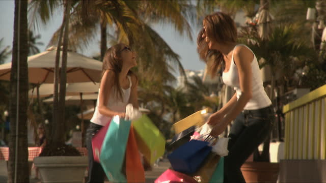 SLO MO MS Young woman and girl (10-11) holding shopping bags on sidewalk, laughing / South Beach, Florida, USA