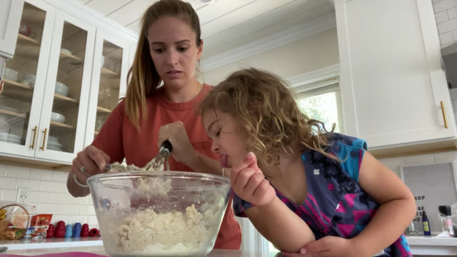 vídeos de stock, filmes e b-roll de young woman and girl prepare food together in the kitchen (audio) - nojo