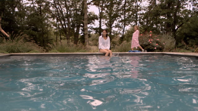 slo mo ws zoom in young woman and girl watching boy dive into swimming pool/connecticut, usa - wrapped in a towel stock videos and b-roll footage