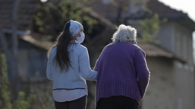 vídeos y material grabado en eventos de stock de joven y abuela para dar un paseo por el barrio al atardecer mientras están en cuarentena covid-19. ambos llevaban máscaras protectoras. ayudar a la mano de un cuidador en el hogar. - rutina