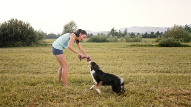 SLO MO Young woman and her Border Collie dog pulling rope outside