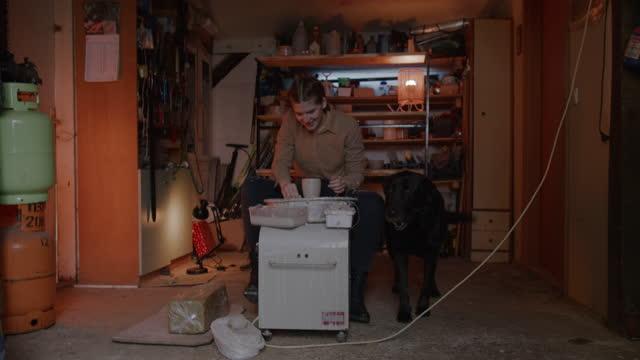 vidéos et rushes de slo mo jeune femme et son chien entrent dans un atelier de poterie - poterie