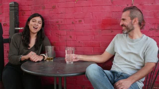 stockvideo's en b-roll-footage met young woman and man having cheerful conversation at outdoor café - hanenkam haardracht