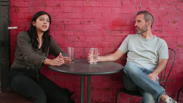 stockvideo's en b-roll-footage met ws young woman and man having conversation at outdoor café - hanenkam haardracht