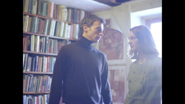 Young woman and man in a room standing near a large bookshelf.