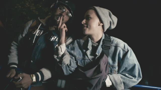 vídeos de stock, filmes e b-roll de young woman and man smoking cigarette at night - jaqueta jeans