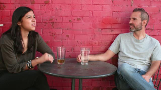 stockvideo's en b-roll-footage met young woman and man speak in wonderment at outdoor café - hanenkam haardracht