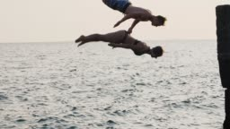 Young woman and man synchronously doing backflip from a pier into the sea during beautiful sunrise, super slow motion