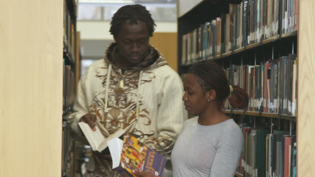 ms young woman and man taking books from shelves at library, orem, utah, usa - orem utah stock videos & royalty-free footage