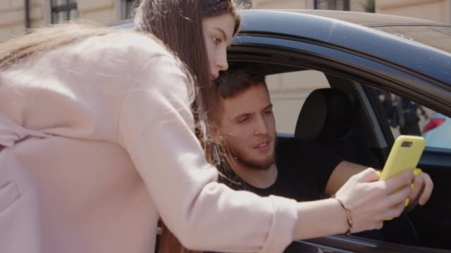 young woman and man using smartphone app to find rideshare and asking driver for directions - parcheggiare video stock e b–roll
