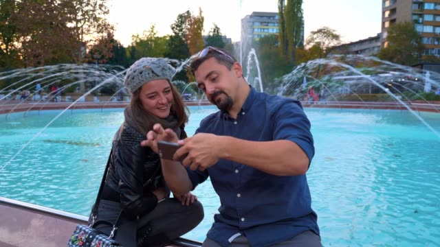 Young woman and man watching something on a smart phone sitting in front of a fountain