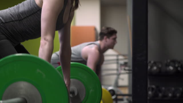young woman and man weightlifting - genderblend stock videos & royalty-free footage
