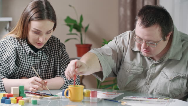 Young woman and man with development disability painting together