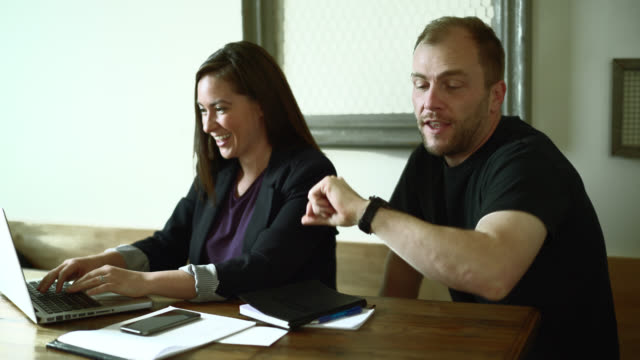 Young woman and man working together with documents on PC laptop