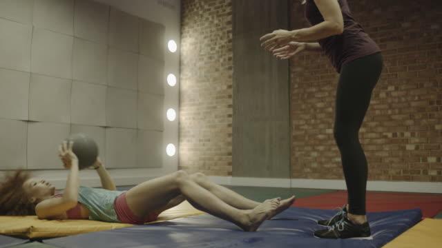 vídeos y material grabado en eventos de stock de young woman and personal trainer exercising abdomen - sólo mujeres jóvenes