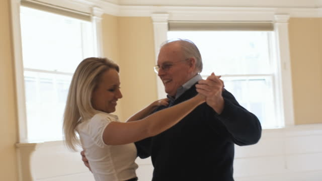 slo mo, cu, young woman and senior man dancing in empty room, hingham, massachusetts, usa - tangoing stock videos & royalty-free footage