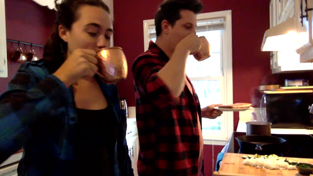 vídeos de stock e filmes b-roll de young woman and young man in kitchen share a celebratory toast with friends over video call - vida real