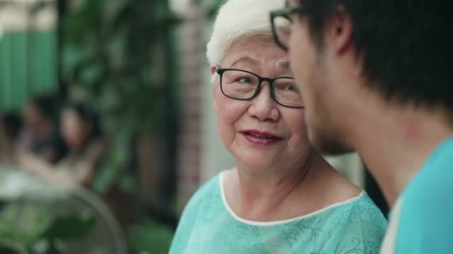 young woman and young man spending time with grandmother - asian stock videos & royalty-free footage