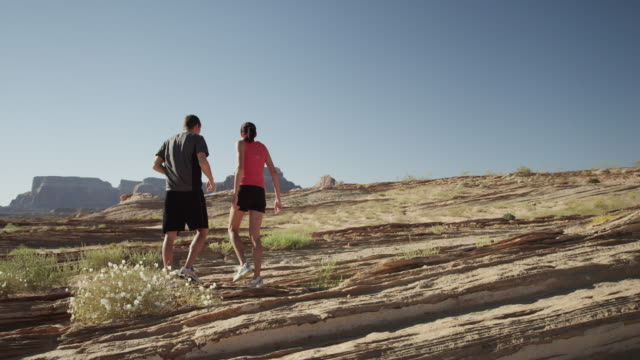 WS DS Young woman and young man stretching and jogging in desert landscape / Lake Powell, Utah, USA