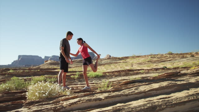 ws ds young woman and young man stretching in desert landscape / lake powell, utah, usa - lake powell stock videos & royalty-free footage