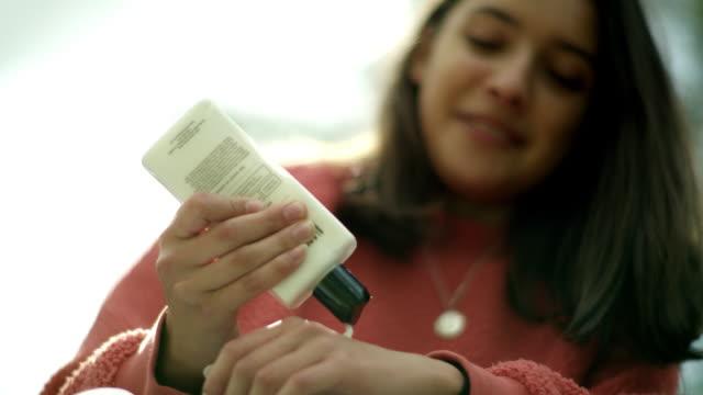 vídeos y material grabado en eventos de stock de young woman applying hand sanitizer - sólo una adolescente