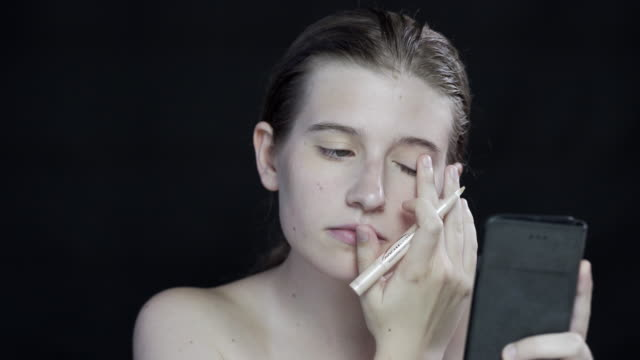 A young woman applying her make-up, using he phone as a mirror, on a black background