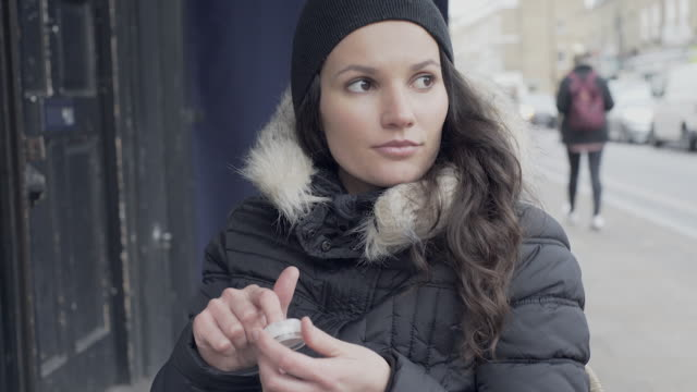 A young woman applying lip gloss in winter.A young woman applying lip gloss outside a cafe during winter.