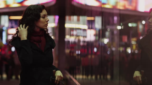 MS Young woman applying lipstick in front of window display in Times Square at night / New York City, New York State, USA