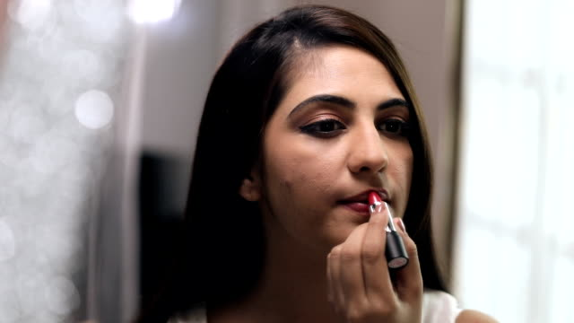vidéos et rushes de young woman applying lipstick on her lip, delhi, india - rouge à lèvres rouge