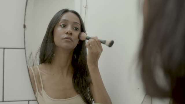 young woman applying make up in mirror - pardo brazilian stock videos & royalty-free footage