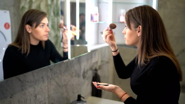 vídeos y material grabado en eventos de stock de mujer joven que aplica maquillaje - cuidado de la piel