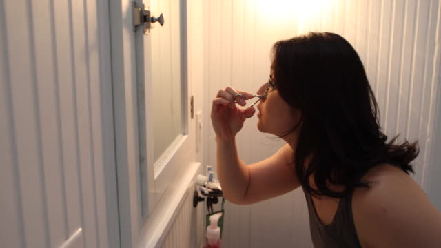 young woman applying makeup, getting ready for work and the start of her day. - pampering self bildbanksvideor och videomaterial från bakom kulisserna