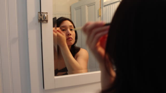 Young woman applying makeup, getting ready for work and the start of her day.