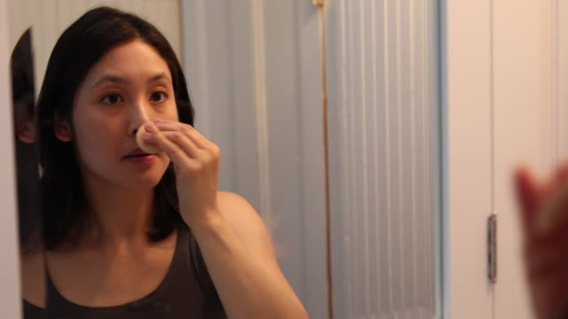 young woman applying makeup, getting ready for work and the start of her day. - cura della persona video stock e b–roll