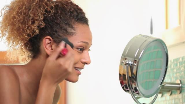 CU PAN Young woman applying make-up in bathroom / Richmond, Virginia, USA