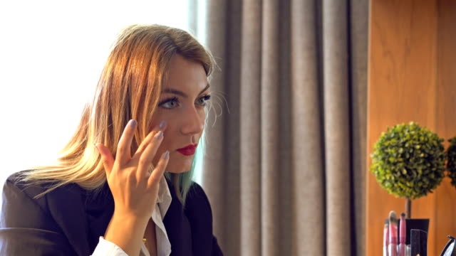 Young woman applying make-up in front of the mirror