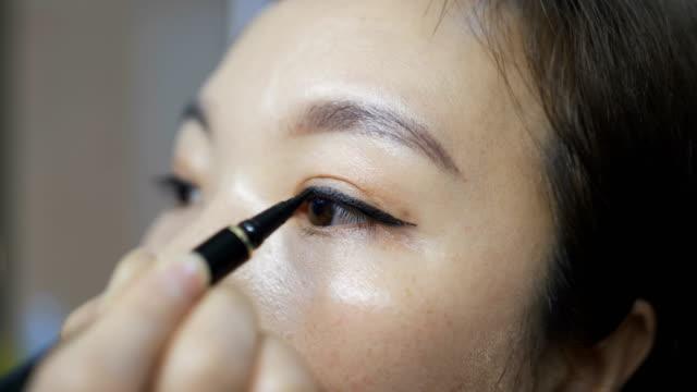 vidéos et rushes de jeune femme appliquant le maquillage - appliquer