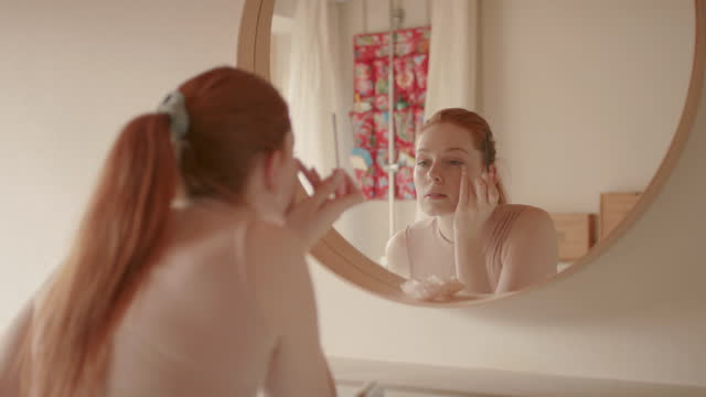 young woman applying mascara in front of mirror - white caucasian stock videos & royalty-free footage