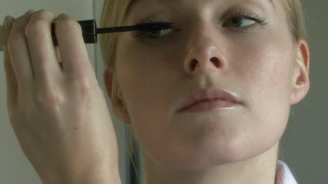 Young woman applying mascara; UK
