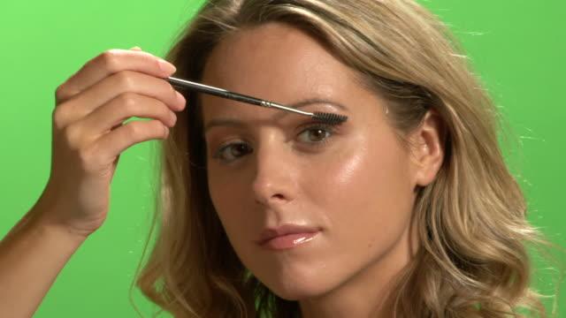 CU Young woman applying mascara
