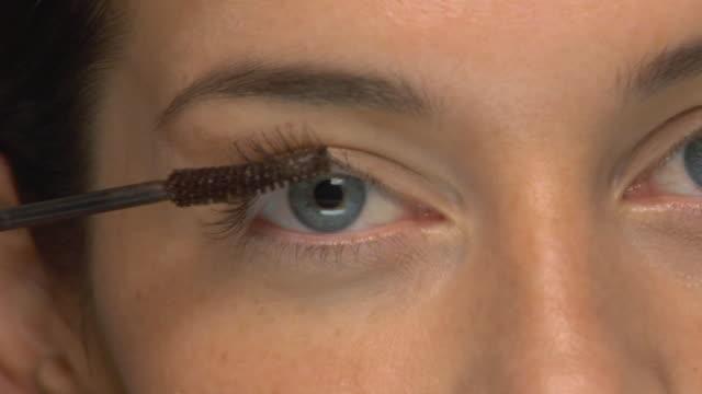 ECU, Young woman applying mascara