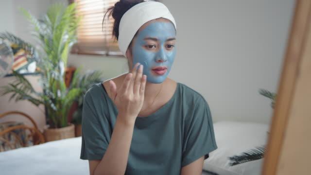 彼女の顔の皮膚にマスクを適用する若い女性。 - 粘土点の映像素材/bロール