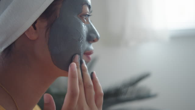 young woman applying mask on her facial skin. - scrubbing stock videos & royalty-free footage