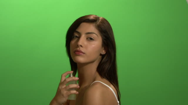 MCU Young woman applying perfume