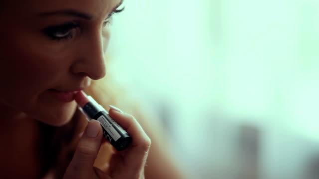 vídeos de stock, filmes e b-roll de cu jovem mulher aplicando batom rosa - aperfeiçoamento pessoal