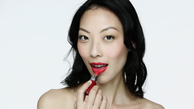young woman applying red lipstick - medium length hair stock videos & royalty-free footage